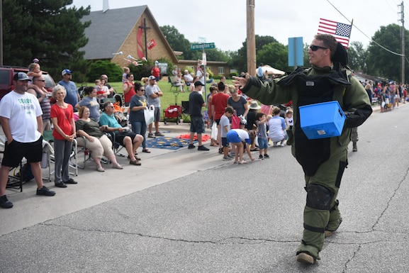 Staff Sgt. Zachary Logan, 22nd Civil Engineer Squadron explosive ordnance disposal team leader, throws candy to spectators watching the parade July 4, 2019, in Derby, Kan. EOD drove their work vehicle in the parade and wore a bomb suit, which is used while defusing unexploded ordnances. (U.S. Air Force photo by Airman 1st Class Alexi Myrick)