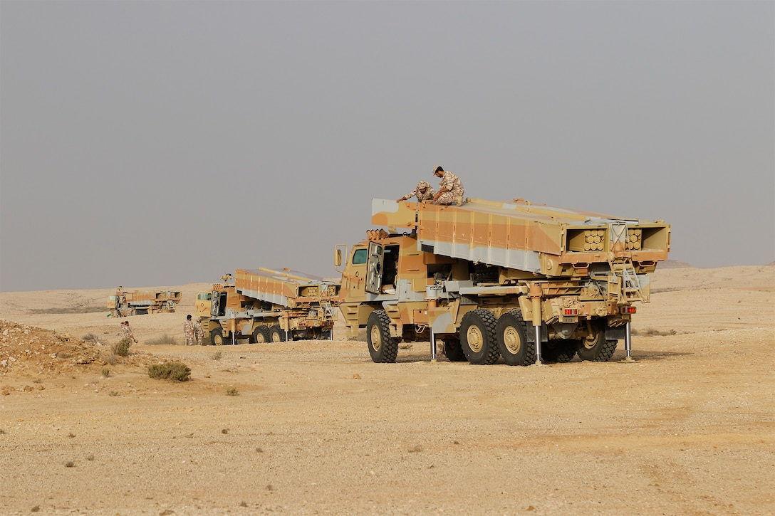 Soldiers atop large vehicles.