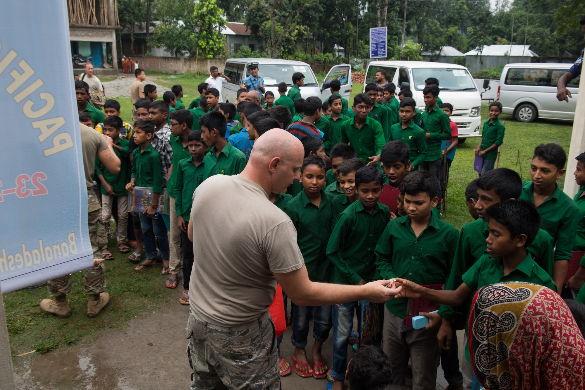 U.S. Air Force Staff Sgt. Danny Mclain, 18th Civil Engineer Squadron structural craftsman, Kadena Air Base, Japan, hands out candy to students during Pacific Angel 19-1 in Lalmonirhat, Bangladesh, June 25, 2019. These humanitarian assistance exercises build relationships between Bangladesh, the United States, and other regional nations, promoting military-civilian-nongovernmental organization cooperation. (U.S. Air Force photo by Staff Sgt. Ramon A. Adelan)