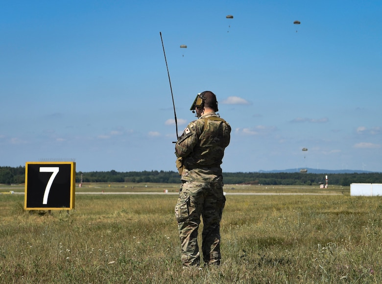 U.S. Air Force Tech. Sgt Joshua Todd, 435th Contingency Response Squadron drop zone controller, monitors parachutists during personnel drops over Ramstein Air Base, Germany, July 2, 2019. The 435th CRG conducts approximately 24 training jumps annually, allowing personnel to maintain proficiency and readiness.