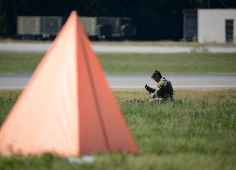 U.S. Staff Sgt. Mark Melchiori, 435th Security Forces Squadron jump master, gathers his parachute and gear during personnel drops over Ramstein Air Base, Germany, July 2, 2019. The 86th Operations Support Squadron and the 37th Airlift Squadron coordinated to accomplish the drop over Ramstein's airfield despite airlift operations.