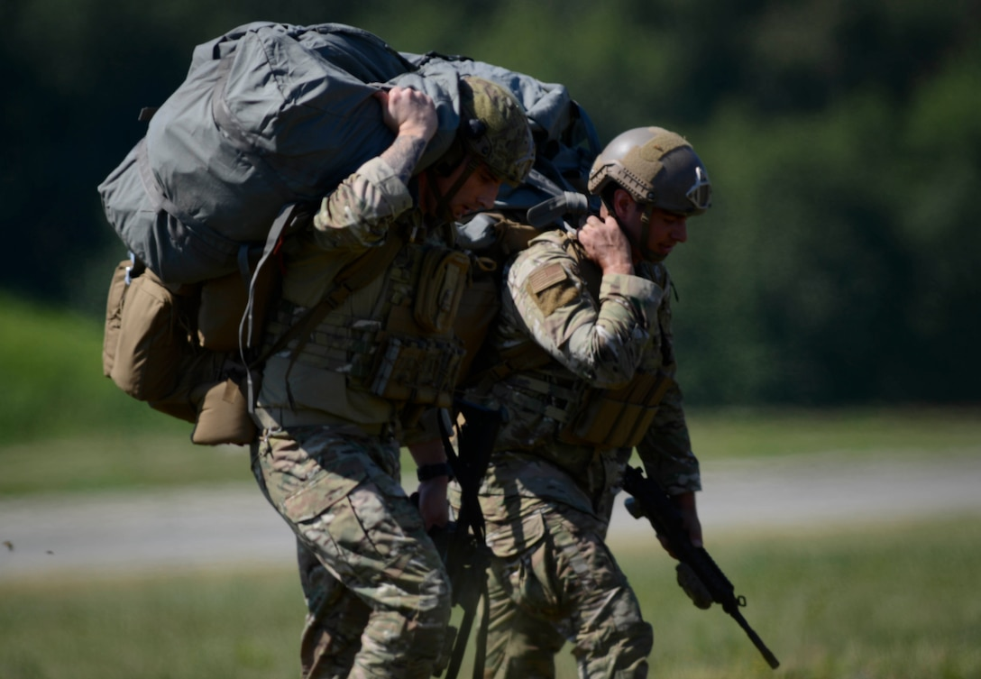U.S. Air Force Tech. Sgt. Brandon Bixby, left, 435th Security Forces Squadron contingency response team chief, and Tech. Staff Sgt. Mark Melchiori, 435th SFS jump master, head to the meeting point during personnel drops over Ramstein Air Base, Germany, July 2, 2019. Approximately 40 personnel participated in the jump to maintain proficiency on static line parachute operations.