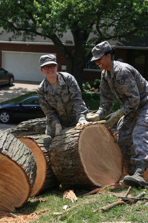 Tech. Sgt. Aubrey Booher (left) and Staff Sgt. Adrienne Zizza, both from the 445th Aerospace Medicine Squadron, remove trees from the home a 445th Airman, June 2, 2019.