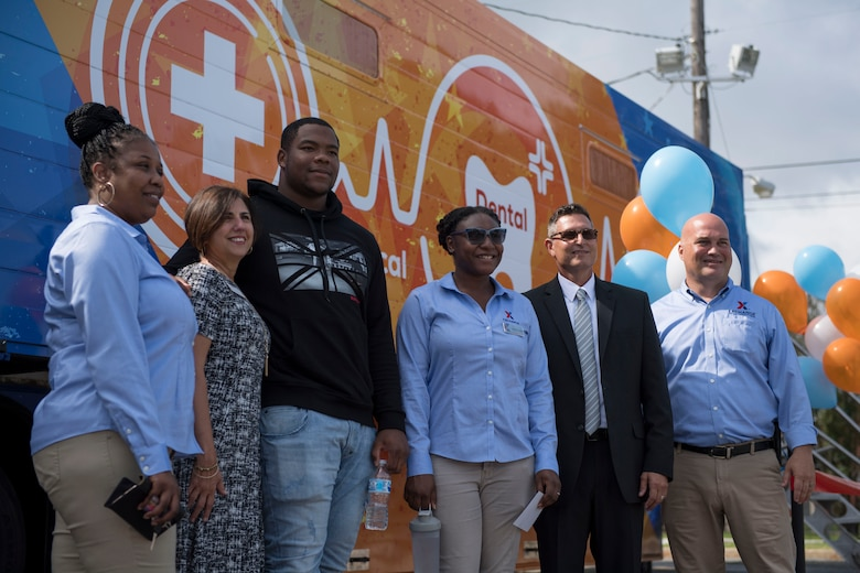 National Football League player Daron Payne takes a photo with Army and Air Force Exchange Services employees during the grand opening of the Dentrust Optimized Care Solutions mobile treatment facility at Joint Base Langley-Eustis, Virginia, July 8, 2019.