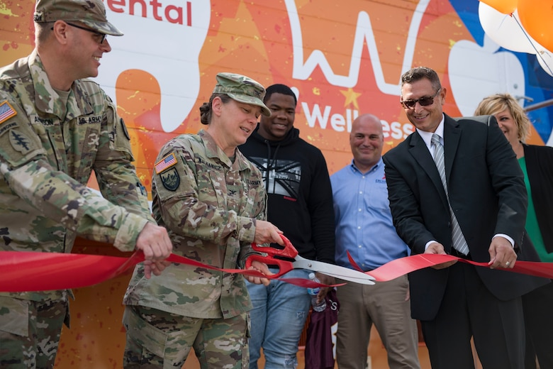 U.S. Army Col. Jennifer S. Walkawicz, 733rd Mission Support Group commander, cuts a ribbon during the grand opening of the Dentrust Optimized Care Solutions mobile treatment facility at Joint Base Langley-Eustis, Virginia, July 8, 2019.