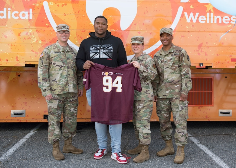 National Football League player Daron Payne, Washington Redskins defensive tackle, and Fort Eustis personnel hold up a football jersey during the grand opening of the Dentrust Optimized Care Solutions mobile treatment facility at Joint Base Langley-Eustis, Virginia, July 8, 2019.
