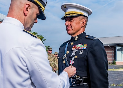 Navy Admiral awarding a medal to Marine Corps Lt. Col. During a retirement ceremony.