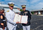 Defense Logistics Agency Land and Maritime Commander Navy Rear Adm. John Palmer presents Marine Corps Lt. Col. Kirk Greiner, Operational Support Division Land Customer Operation division chief, with a certificate of retirement during Greiner's July 3 retirement ceremony at the Navy Reserve Center Rickenbacker Air Base in Columbus, Ohio.