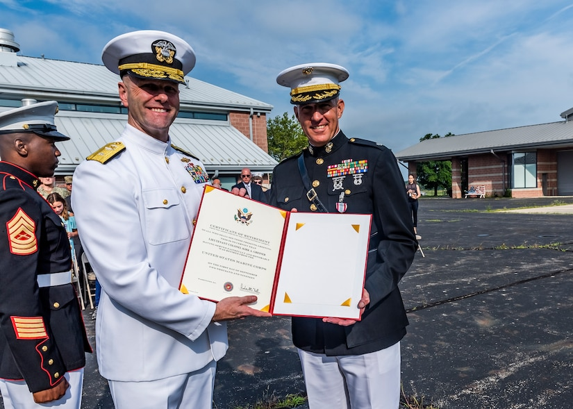 Navy rear admiral lower half presenting a retirement certificate to a Marine Corps lieutenant colonel during a retirement ceremony.