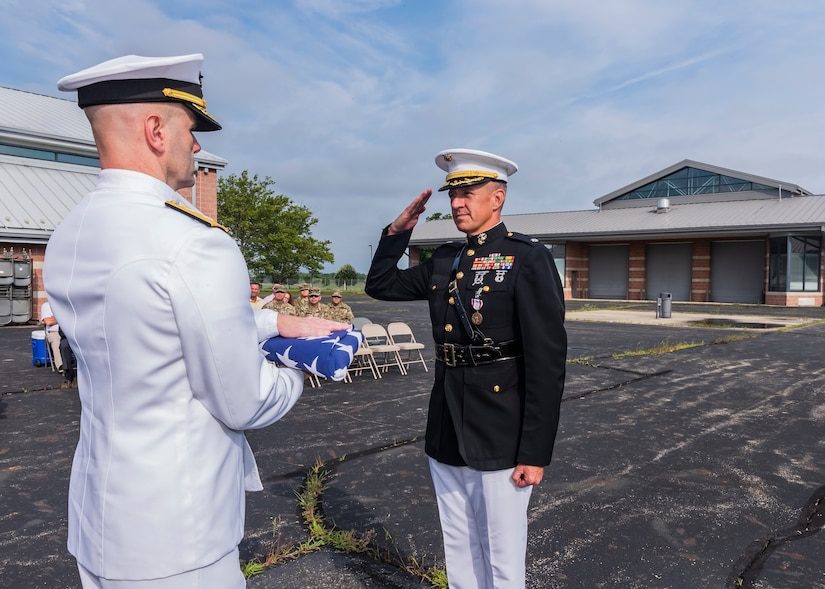 Navy rear admiral lower half presenting a United States Flag to a Marine Corps lieutenant colonel during a retirement ceremony.