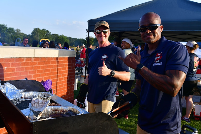 Two first sergeants pose for a photo by the grill at Liberty Fest.