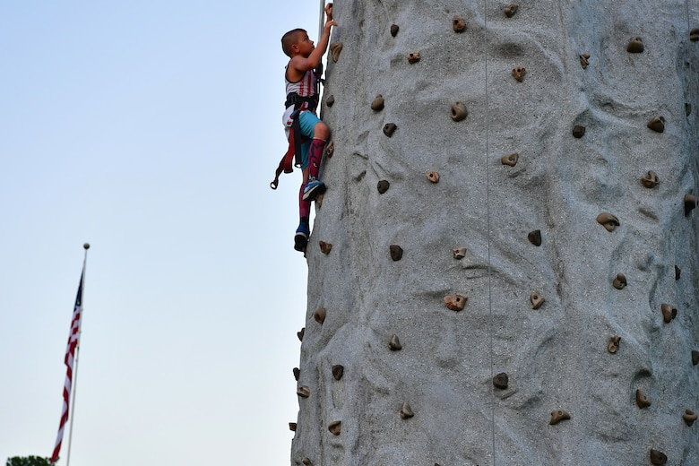 A child climbs a rock wall at the Liberty Fest.