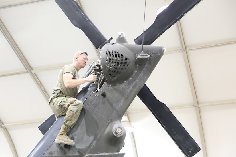 Sgt. Jerry Karnes, a helicopter repairer with Company D, 8th Battalion, 229th Aviation Regiment, 244th Combat Aviation Brigade, performs 120 hour maintenance checks and services on a UH-60 Blackhawk helicopter, June 26, 2019 at Camp Buehring, Kuwait