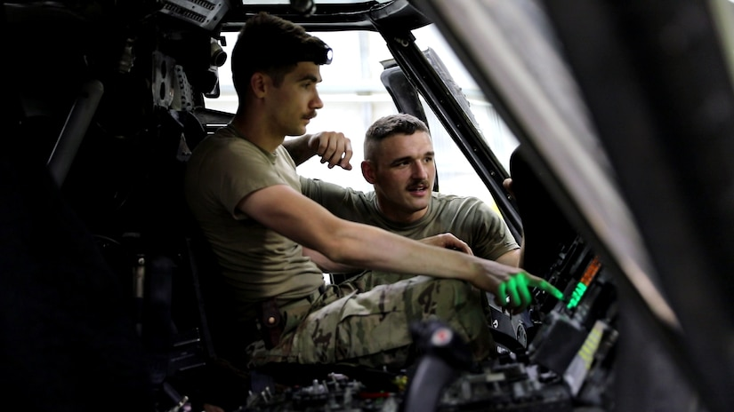 Sgt. Johnathan Kessel, an aviation component repairer (right) and Spc. James Chaffins, an aviation electrician both with the Kentucky Army National Guard's 2nd Battalion, 147th Aviation Regiment, currently assigned to D Company, 8th Battalion, 229th Aviation Regiment, 244th Combat Aviation Brigade, troubleshoot a suspected malfunctioning UH-60 Blackhawk helicopter warning light, June 26, 2019, at Camp Buehring, Kuwait.