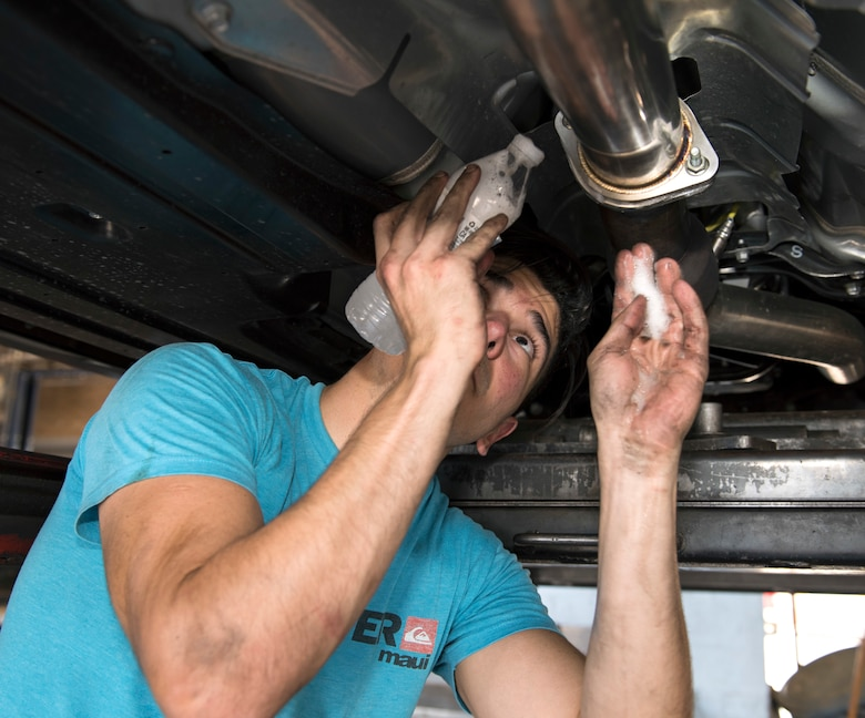 Senior Airman Igor Pacheco, 56th Medical Support Squadron lab technician, applies soapy water to a clamp on middle piping during an exhaust system replacement for his vehicle June 29, 2019, at the Auto Hobby Shop at Luke Air Force Base, Ariz.