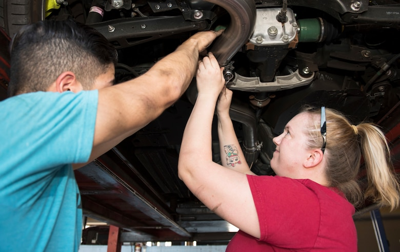 Senior Airman Igor Pacheco, 56th Medical Support Squadron lab technician (left), and Senior Airman Samantha Campbell, 56th Civil Engineer Squadron Airman dorm leader, work together to replace an exhaust system in a vehicle June 29, 2019, in the Auto Hobby Shop at Luke Air Force Base, Ariz.