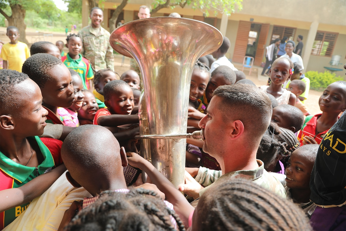 A soldier plays an instrument while surrounded by children.