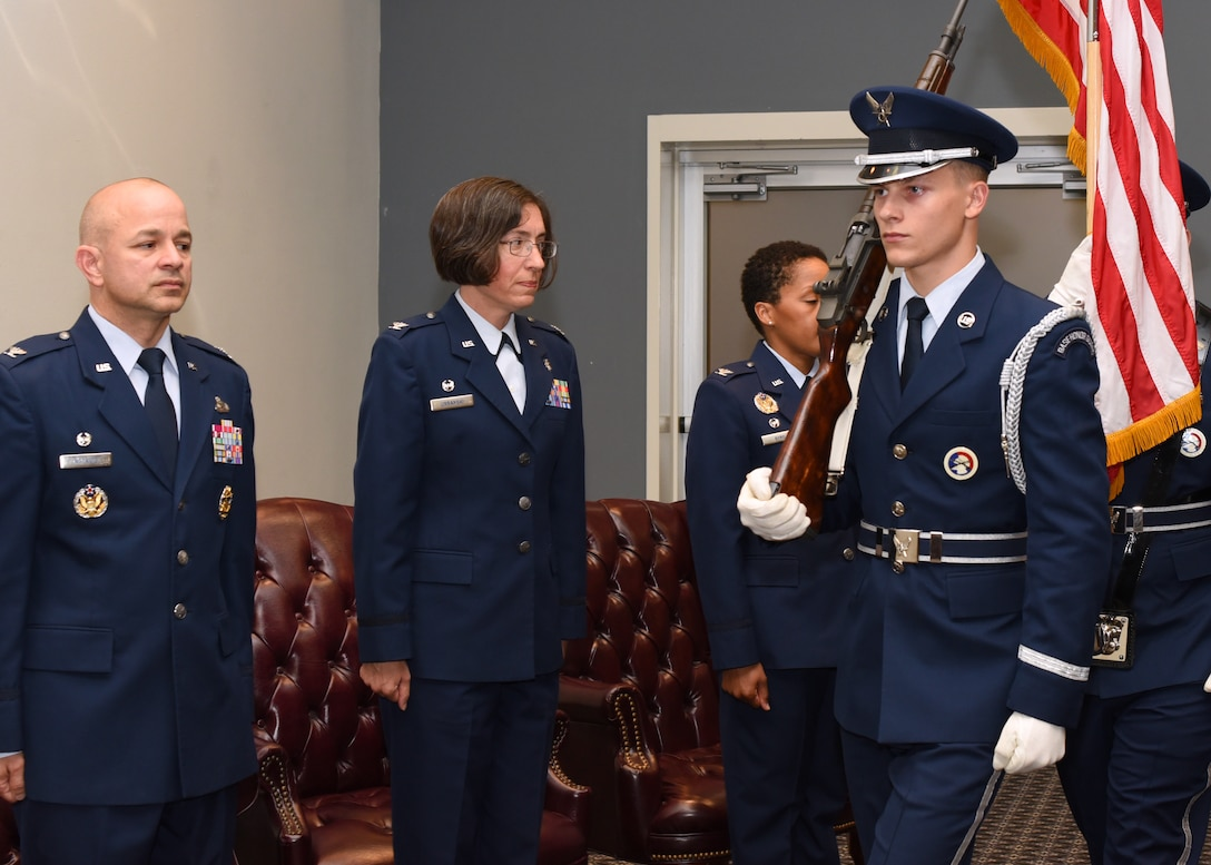 U.S. Air Force Col. Andres Nazario, 17th Training Wing commander, Col. Janet Urbanski, 17th Medical Group outgoing commander, and Col. Lauren Byrd, 17th MDG incoming commander show respect by standing at attention for the posting of colors at the 17th MDG Change of Command Ceremony at the event center on Goodfellow Air Force Base, Texas, July 8, 2019. The posting of colors is a formality done at the beginning of military ceremonies and public events by the color guard to properly position the flags. (U.S. Air Force photo by Airman 1st Class Abbey Rieves/Released)