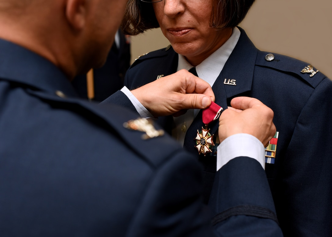 U.S. Air Force Col. Andres Nazario, 17th Training Wing commander, pins Col. Janet Urbanski, 17th Medical Group outgoing commander, with the Legion of Merit medal for her accomplishments as commander during the 17th MDG Change of Command Ceremony held at the event center on Goodfellow Air Force Base, Texas, July 8, 2019. Urbanski was awarded the accolade for praiseworthy service over the past two years at Goodfellow. (U.S. Air Force photo by Airman 1st Class Abbey Rieves/Released)