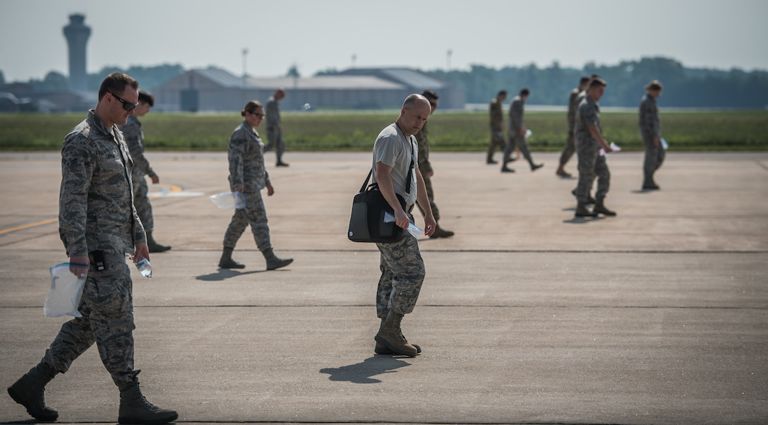 Master Sgt. Jonathon Tolbert, 375th Air Mobility Wing foreign object debris monitor, center,  walks the flightline looking for possible aircraft damaging debris with fellow Team Scott Airmen during the weekly FOD walk, July 9, 2019, Scott Air Force Base, Illinois. (U.S. Air Force photo by Christopher Parr)