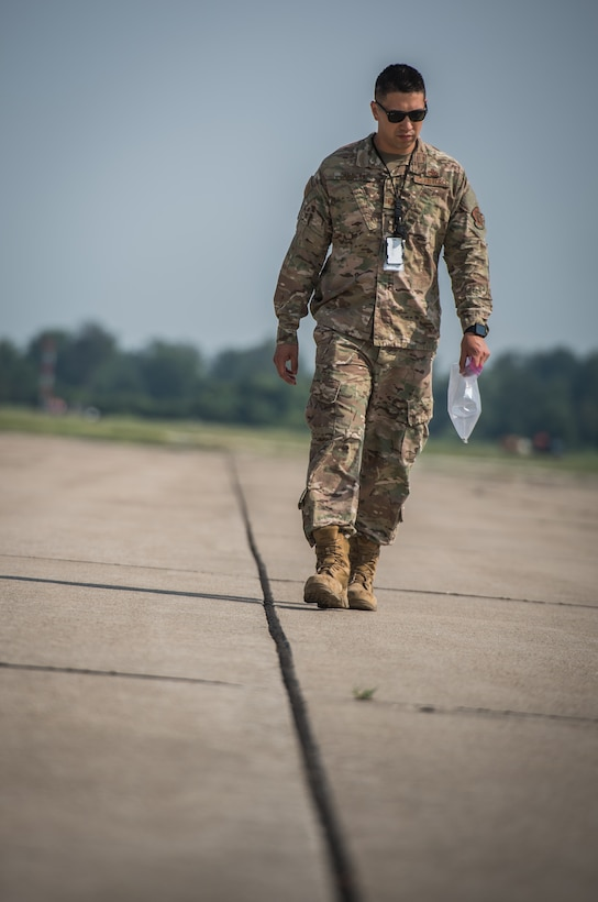 Master Sgt. Sandro Cardona, flightline expediter, 932nd Airlift Wing Maintenance Squadron, scans the flightline for debris during the weekly foreign object debris (FOD) walk, July 9, 2019, Scott Air force Base, Illinois. (U.S. Air Force photo by Christopher Parr)