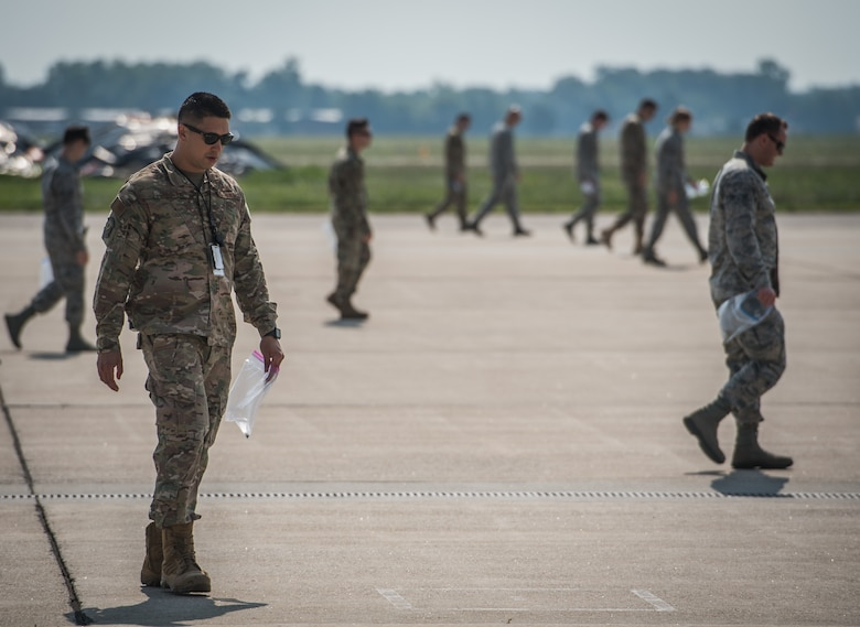 Master Sgt. Sandro Cardona, flightline expediter, 932nd Airlift Wing Maintenance Squadron,  along with Team Scott Airmen, scans the flightline for debris during the weekly foreign object debris (FOD) walk, July 9, 2019, Scott Air force Base, Illinois. (U.S. Air Force photo by Christopher Parr)