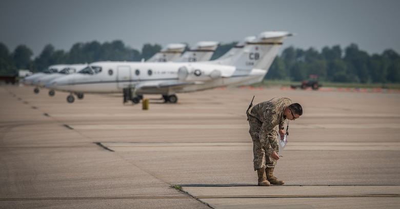 Master Sgt. Sandro Cardona, flightline expediter, 932nd Airlift Wing Maintenance Squadron, picks up potentially hazardous debris from the flightline during the weekly foreign object debris (FOD) walk, July 9, 2019, Scott Air force Base, Illinois.  FOD can be harmful to aircraft if it is sucked into the engines, possibly causing damage to the high-precision engines and other vital systems. (U.S. Air Force photo by Christopher Parr)