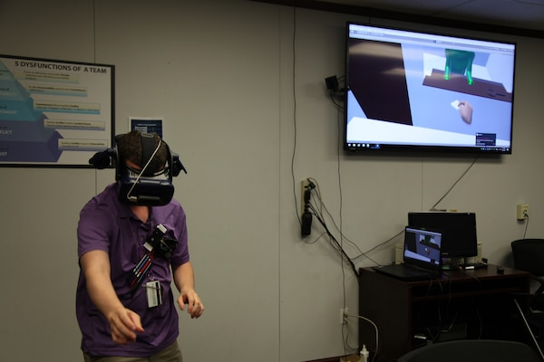 Computer Engineer Daniel Stith shows how to use the hands-free headset for the virtual reality simulation.