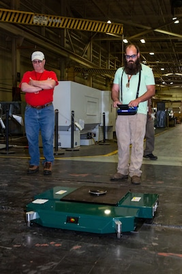 Production Machinery Mechanic Ethan Holland operates the TK-EVO Heavy Lifting Device using a remote-controlled device.