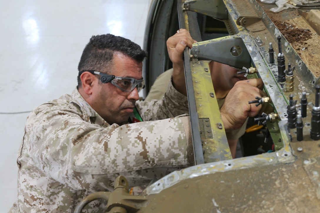 2nd Lt. Raad Alzubi, Royal Jordanian Air Force, aligns a fabricated sheet metal piece to a UH-60 Blackhawk helicopter during a subject matter expert exchange with the U. S. Army's 1106th Aviation Group at the King Abdullah II Air Base in Amman, Jordan, June 19, 2019. (U.S. Army National Guard photo by Staff Sgt. Veronica McNabb)