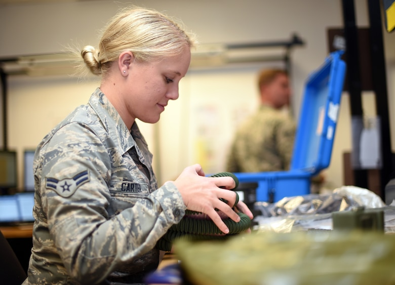 U.S. Air Force Airman 1st Class Hailey Carter, 60th Operations Support Squadron Aircrew Flight Equipment technician, inspects aircrew equipment July 9, 2019, at Travis Air Force Base, California. Travis' AFE flight works to keep aircrew flight equipment in good working condition thereby safeguarding aircrew personnel in the event of dangerous situations. (U.S. Air Force photo by Senior Airman Christian Conrad)