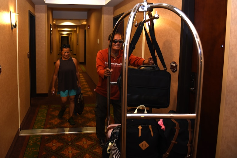 Jose and Angelita Peralta, West Westwind Inn guests, bring their luggage to their room July 8, 2019, at Travis Air Force Base, California. Westwind Inn is one of the finalists for the Air Force's 2019 Innkeeper Award after being named the best in Air Mobility Command. The Innkeeper Award is an annual honor recognizing excellence in the service's lodging operations. (U.S. Air Force photo by Airman 1st Class Cameron Otte)