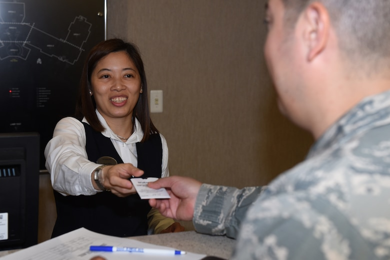 Rachel Natalya, Westwind Inn receptionist, hands U.S. Air Force Staff Sgt. Jesus Beltran, Westwind Inn guest, a room key July 8, 2019, at Travis Air Force Base, California. Westwind Inn is one of the finalists for the Air Force's 2019 Innkeeper Award after being named the best in Air Mobility Command. The Innkeeper Award is an annual honor recognizing excellence in the service's lodging operations. (U.S. Air Force photo by Airman 1st Class Cameron Otte)
