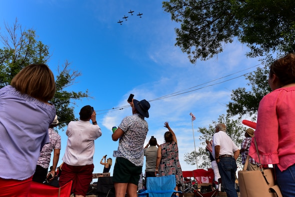 Members from Laughlin Air Force Base and Del Rio, Texas, watch a formation of T-6 Texan II aircraft fly over the Dr. Arturo Gutierrez Amphitheater by the San Felipe Creek in Del Rio, July 4, 2019. The city of Del Rio and Laughlin Air Force Base joined forces to celebrate the Fourth of July with music by artists from Del Rio, including Radney Foster, William Beckmann, Angel Baena and River Tramps and a fireworks display. (U.S. Air Force photo by Senior Airman Anne McCready)