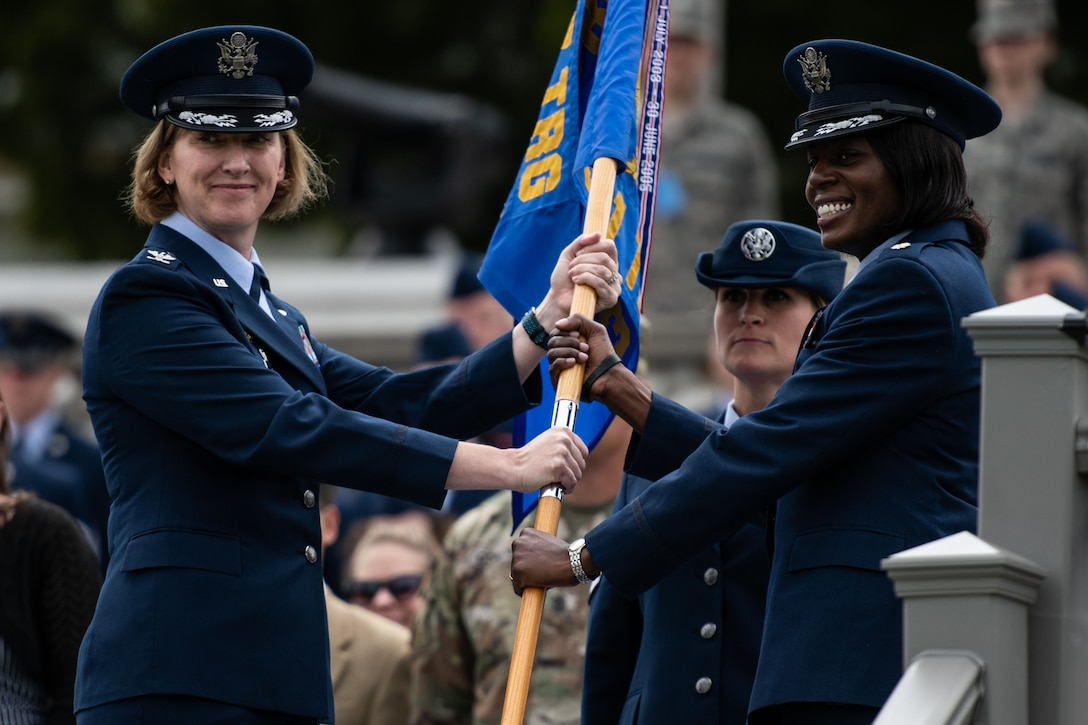 U.S. Air Force Col. Stephanie Kelley, 517th Training Group commander, passes the guidon to Lt. Col. Nicci Rucker, 311th Training Squadron incoming commander, during the change of command ceremony on Soldier Field at the Presidio of Monterey, California, July 8, 2019. The change of command ceremony is a military tradition which illustrates the formal transfer of authority by passing the guidon from the departing commander to the incoming commander via the overseeing officer. (Courtesy Photo)
