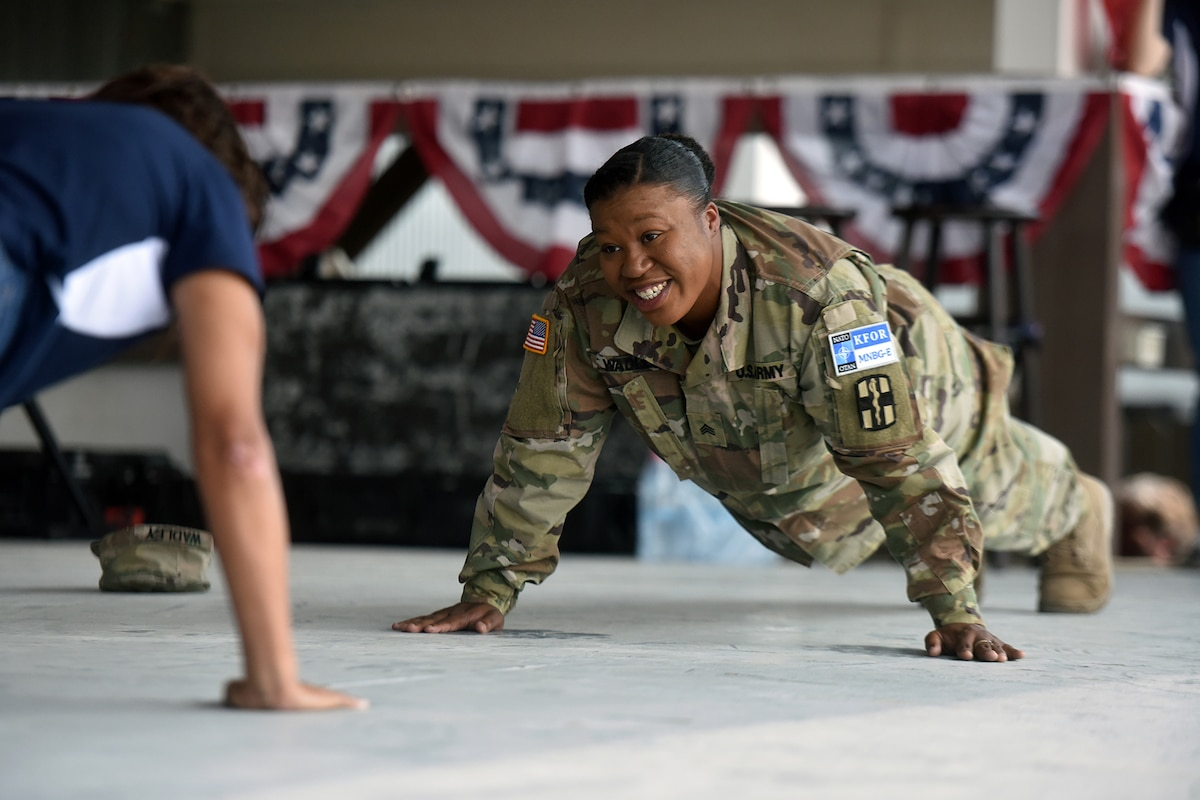 A soldier and an actress assume a plank position on the floor.