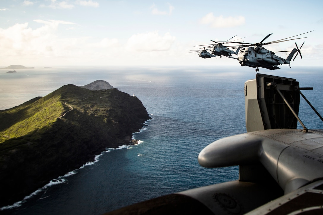 Helicopters fly over Oahu.