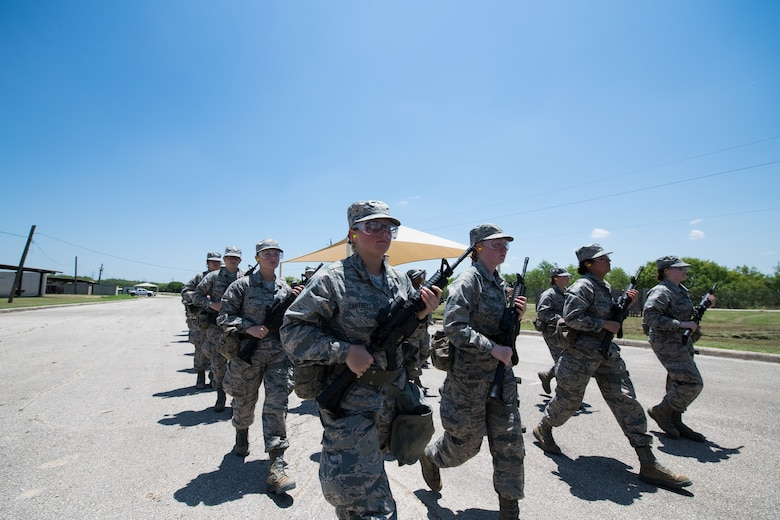 U.S. Air Force basic training trainees march back from the firing range after a weapons familiarization course, June 8, 2019, at Joint Base San Antonio-Medina Annex. BMT trainees were the first to experience M-4 Carbine Weapons Familiarization Course at the new facility, which closed in November 2018, due to improper rainwater drainage. The firing range allows instructors to train 244 BMT trainees daily, four days a week, qualifying more than 40,000 BMT trainees in the M-4 carbine annually. (U.S. Air Force photo by Sarayuth Pinthong)