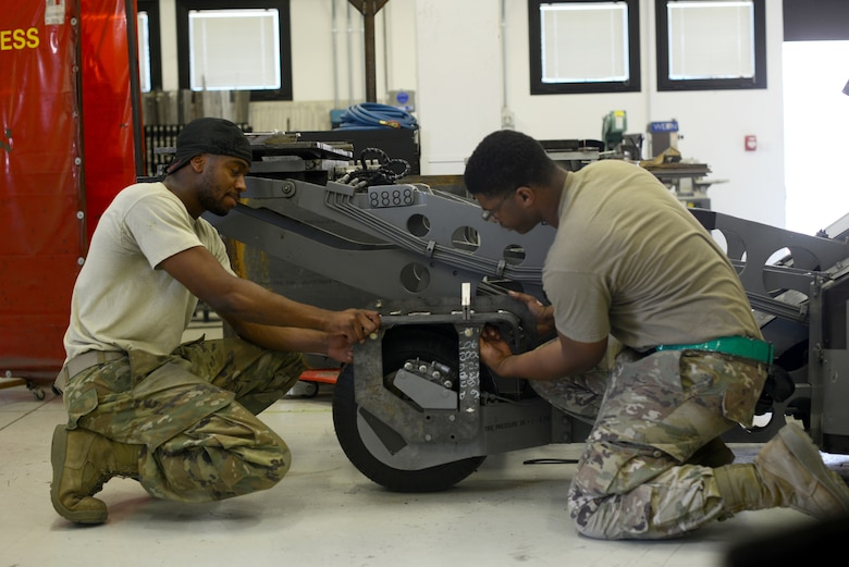 U.S. Air Force Airman Basic Jeffery Jenkins, left, and Senior Airman Michael Taliaferro, right, aircraft structural maintenance technicians from the 31st Maintenance Squadron, mount the MJ-1 STEP onto the MJ-1, July 1, 2019 at Aviano Air Base, Italy. There are seven flights within the 31st MXS, including accessories, aerospace ground equipment, avionics, programs, fabrication, maintenance, and test measurement and diagnostic equipment. (U.S. Air Force photo by Airman 1st Class Ericka A. Woolever)