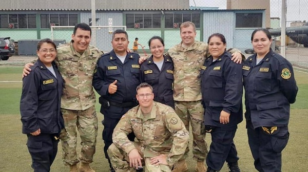 Sgt. 1st Class Hector Guillen, left, Sgt. Brad Miller, bottom middle, and Master Sgt. Evan McDonough, right, pose for a photo with members of the Peruvian National Police July 2, 2019, in Lima, Peru. Members of the WVARNG trained more than 120 members of the Peruvian Armed Forces and the Peruvian National Police on a variety of aeromedical topics during a week-long subject matter exchange.