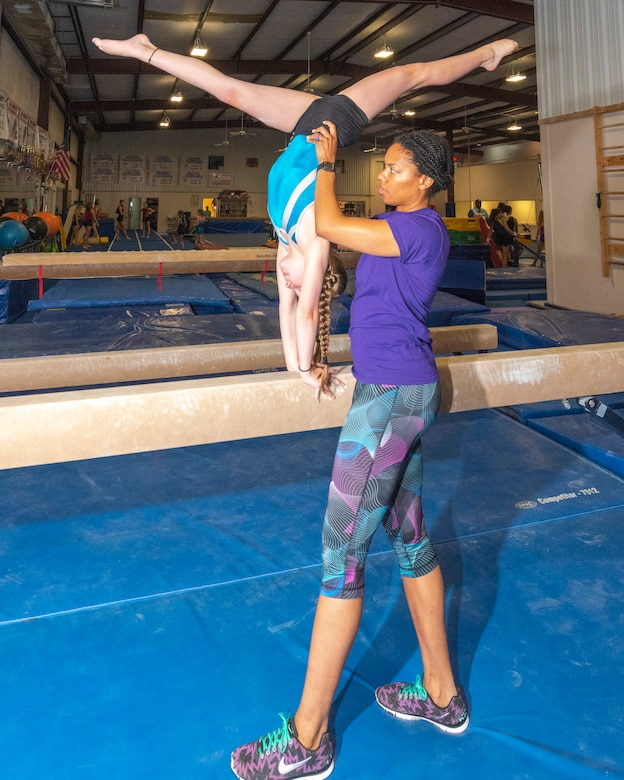 """Senior Airman Kaylan James, traditional reservist assigned to the 913th Airlift Group, coaches a young gymnast on form and technique at a local gym June 20, 2019. In her """"free time"""", she shows her dedication by coaching gymnastics within the community. Senior Airman James' future aspirations are to commission and become an Aeromedical Evacuation Nurse. (U.S. Air Force Reserve photo by Maj. Ashley Walker)"""