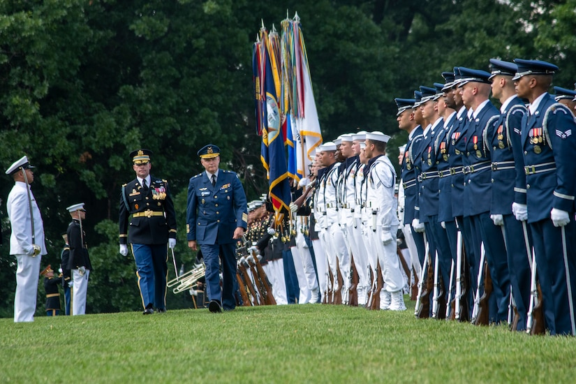 Military officers walk in front of a formation of troops.