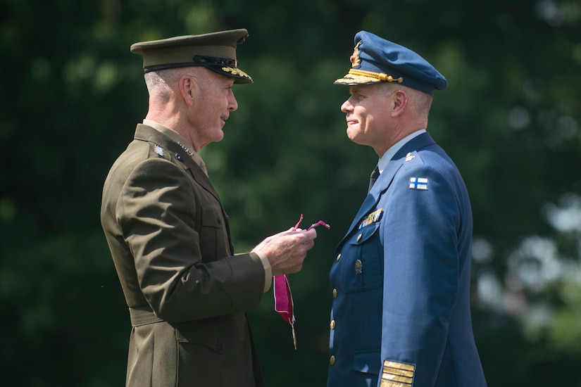 A U.S. military officer presents a medal to a Finnish officer.