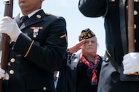 Lt. Col. (ret.) Jennifer Pritzker, founder of the Pritzker Military Museum and Library in Chicago, salutes the color guard