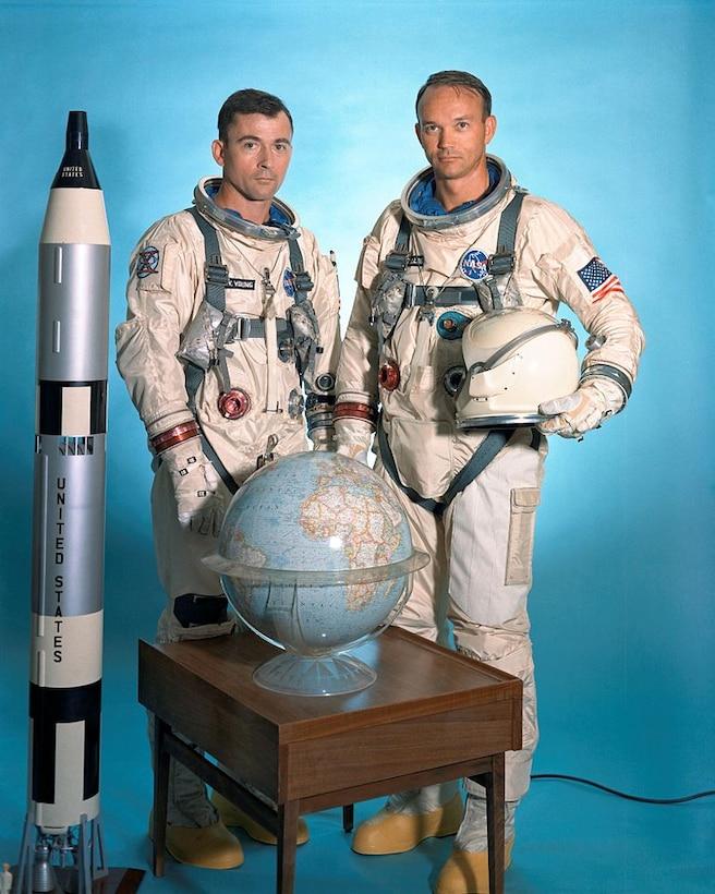 Men pose beside rocket model