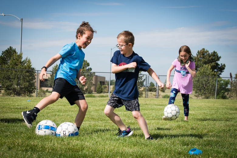 Children from the Schriever Air Force Base School Age Care program, play soccer during the Air Force Specialty Camp at the Child Development Center at Schriever AFB, Colorado, July 8, 2019. During the event, children aged 6 to 11, learned basic soccer and motor skills while working on their interpersonal skills. (U.S. Air Force photo by 2nd Lt. Idalí Beltré Acevedo)