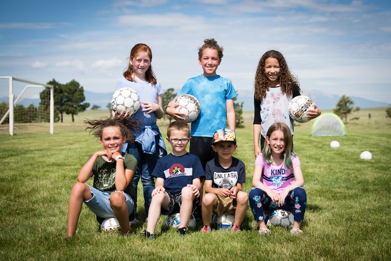 Children from the Schriever Air Force Base Child Development Center School Age Care program gather for a picture during the Air Force Specialty Camp at Schriever AFB, Colorado, July 8, 2019. During the weeklong camp, the kids learned basic soccer skills while playing fun and engaging games. (U.S. Air Force photo by 2nd Lt. Idalí Beltré Acevedo)