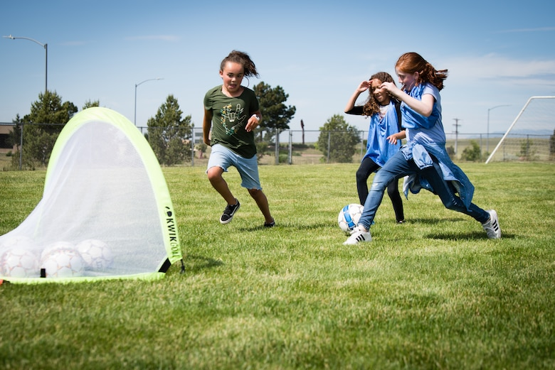 Children from the Schriever Air Force Base Child Development Center School Age Care program, play soccer during the Air Force Specialty Camp at Schriever AFB, Colorado, July 8, 2019. This is the second time Schriever AFB hosted the Air Force Specialty Camp for the School Age Care program children. (U.S. Air Force photo by 2nd Lt. Idalí Beltré Acevedo)