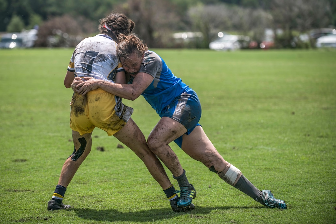 One muddy athlete grips another around the waist and leans in to tackle her.