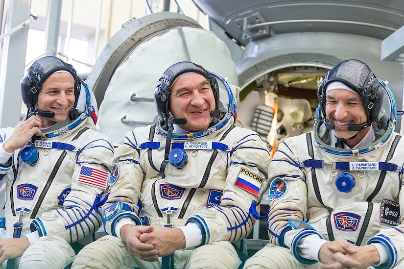 Three astronauts pose for photo.